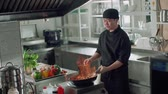 персонал : chef works mixed colored roasting vegetables in the wok-tossing and flames , kitchen Asian restaurant, slow motion