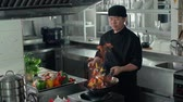 highdef : Asian chef works with the wok with flames roasting mixed colorful vegetables , restaurant kitchen , slow motion