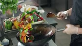 flambe : close-up cook actively roasting mixed colorful vegetables wok-tossing in the kitchen of an Asian restaurant, slow motion