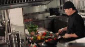 flambe : the cook is actively roasting mixed colorful vegetables wok-tossing in the kitchen of an Asian restaurant, slow motion Stock Footage