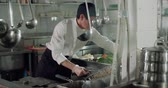 erişte : older experienced Asian chef working in a restaurant kitchen Stok Video
