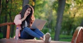 back lit : girl in the park with a laptop, much expresses joy Stock Footage