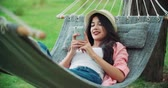 park : beautiful girl with a smartphone on the gammack, enjoy life