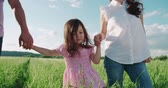 taking away : little Asian girl walking on the green field with their parents, holding hands, slow motion Stock Footage