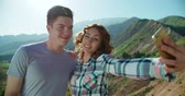 flört : Smart phone selfie - couple taking self portrait using smartphone camera in the background mountains sunset time,slow motion