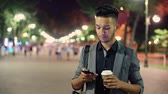 enviar : a young guy walking through the city after work, with coffee in hand, talking on a smartphone Vídeos