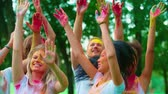 rave : group of young friends in the Park with the colors of Holi, dancing and having fun, close-up