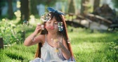 masum : Happy little Asian girl blowing soap bubbles in spring Park. Slow motion