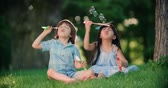 varinha : Happy children Caucasian boy and Asian girl blowing soap bubbles in spring Park, slow motion Vídeos