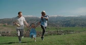 family idyll concept, a young family with a little daughter happily run holding hands in a beautiful mountain place, slow motion