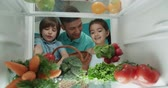 young cute asian family of three choosing vegetables from the fridge - family, wealthiness, healthy way of life concept 4k Stock mozgókép