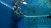 creative : girl in mermaid costume wearing poses underwater in swimming pool