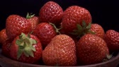 メロウ : Rotation of juicy red strawberries in ceramic dishes on black background. Rotation 360 degrees, closeup. 4K - 50fps