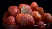 fragaria : Rotate of red strawberries in glassware on black background. Camera rotation 360 degrees, close-up.