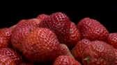 メロウ : Slow motion rotation of fresh strawberries on black background. Close-up, Camera rotation 360 degrees. 動画素材