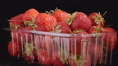 fragaria : Rotation of fresh ripe strawberries in disposable plastic container on black background. Rotation 360 degrees, closeup. 4K - 50fps Stock Footage
