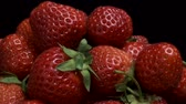 fragaria : Rotation of juicy red strawberries on black background. Rotation 360 degrees, closeup. 4K - 50fps Stock Footage