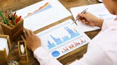 Close-up Of A Businesswoman Analyzing A Colorful Fluctuating Bar Graph On Desk In Office Vidéos Libres De Droits
