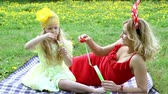 kolaylık : Beautiful woman and girl outdoors blowing bubbles, lying in the grass Stok Video