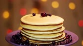 блины : American pancakes with blueberries . On the background of colored lights. Circular motion.
