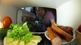 salsicha : The food in the fridge.A woman looking for food in the fridge .