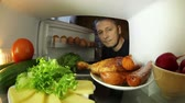 frankfurters : The food in the fridge.Man looking for food in the fridge .The choice between meat or vegetables.