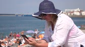 závislost : young woman using a smartphone sitting on the beach.