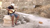 sesleri : A street musician plays a Turkish instrument. A man in a white hat plays a game of baglama.
