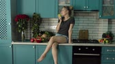 mobile kitchen : A young girl in the kitchen talking on the phone. In the hands of holding a red rose.