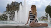 portrait : blonde is sitting on a fountain near a medieval castle and touching sunglasses