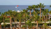 exotikou : KIRIS, TURKEY - MAY, 2017:view of hotel territory near seashore, palms garden, seascape in sunny day, flags are waving, tourists are walking and relaxing on a pier