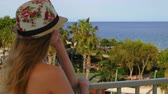 maritime territory : young blonde woman wearing a vivid hat, looking at sea and palm garden, dreaming Stock Footage
