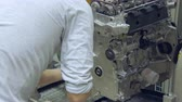 chave inglesa : worker is putting bolts into car engine, modern car production, workshop Vídeos