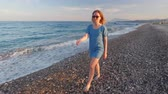seixos : young slim blonde is wearing blue dress and sunglasses is strolling on pebble seashore Vídeos
