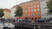 Дания : Copenhagen, Denmark - OCT, 2016:people are walking on a quay, traditional multicolor living houses and sailboats, view from pleasure boat