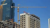 keretében : view on a construction crane and unfinished building in modern city in summer day