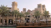 madinat : marine restaurant on quay in sunset time, visitors and workers are strolling between palms