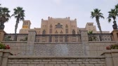 madinat : arabian palace with authentic stone fence in twilight with palm garden and flowerbeds