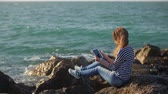 suť : female student is relaxing on a seashore, and watching pictures in her tablet