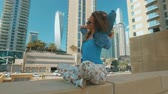 пересек : relaxed blonde girl is sitting, crossed legs, outdoors in Dubai Marina in sunny day