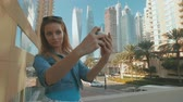 caucasian woman is taking selfies by mobile phone, outdoors in Dubai Marina in sunny day Stok Video