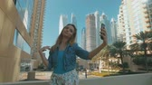 playful woman is taking selfies by mobile phone, outdoors in Dubai Marina in sunny day
