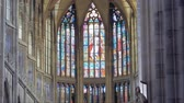 wonderful pictures on stained glasses on windows of gothic cathedral in daytime, inside view
