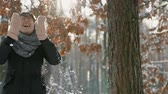 A happy couple, a girl and a young man in a winter park enjoy each others presence and enjoy the falling snow. boy and girl rejoice at falling snow. slow motion 120 fps Filmati Stock