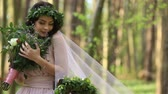 vavřín : Beautiful young brunette bride in laurel wreath with big bouquet of white spring flowers in the forest. Moment of happiness