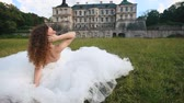 düğün : Pretty young bride in white wedding dress near the castle on green grass lawn looking at the camera Stok Video