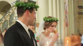 vavřín : Newlyweds wearing green laurel wreathes in the church during wedding ceremony. Bride drinks wine from chalice Dostupné videozáznamy