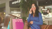 shopping bag sale : attractive brunette is sitting on the bench in shopping center. Talking by phone and smiling. Wearing blue dress , glasses and beautiful ring on her hand.