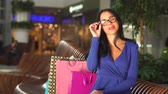 shopping bag sale : beautiful brunette playinging with glasses, smiling and talking with somebody in shopping mall