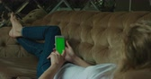 blondehair : Close-up side view of the blonde woman chatting and surfing the net using the mobile phone while laying on the sofa. Stock Footage